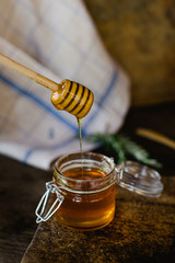 Honey in a glass jar, with a honey scoop.