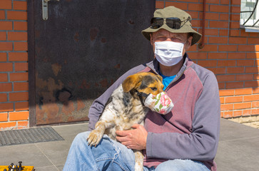 Portrait of Caucasian senior man with mixed breed dog wearing masks sitting on a  threshold while being on Coronavirus COVID-19 quarantine period in Ukraine