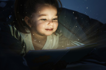 Cute little child reading magic book in darkness