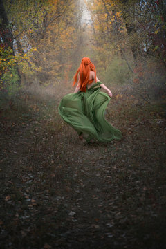 A long-haired red-haired elf girl runs away into the distance through the misty autumn forest. A fairy woman with long hair in a medieval dress.