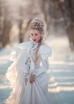 Portrait of an old-fashioned blonde woman in a vintage white dress in a winter forest. A girl with a high, old-fashioned hairdo from the sixteenth century.