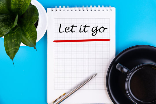 Let It Go text concept written in a notebook with pen, top view.