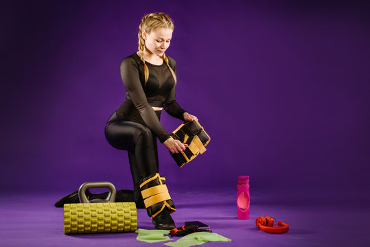 picture of woman, showing process of putting on ankle weights. Young woman, wearing black leggings, is preparing herself for fitness training with weights