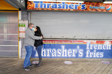 Couple kiss while waiting for fries as coronavirus disease (COVID-19) restrictions are eased at Ocean City in Maryland