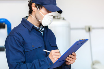 Plumber at work wearing a mask, coronavirus concept