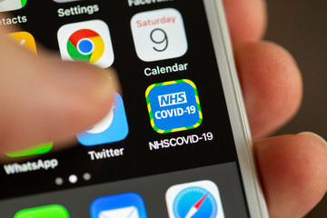 BATH, UK - MAY 9, 2020 : Close-up of the NHS COVID-19 contact tracing app on an iPhone screen with a thumb hovering above it. The app is used to track contact between people with Coranavirus.