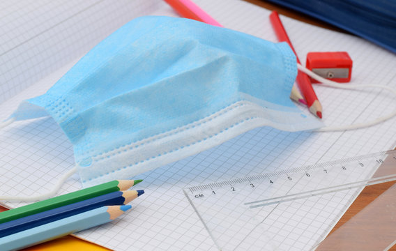 Education in school after pandemic coronavirus with individual protective surgical mask.
