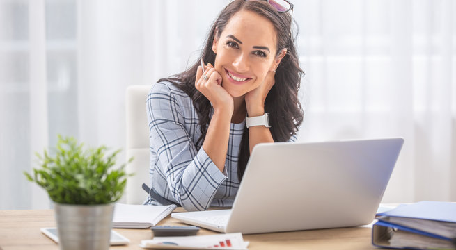 Pretty businesswoman smiles at the camera while sitting at her desk in front of the computer