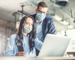 Good looking female and male coworkers look at the computer screen together, wearing face masks