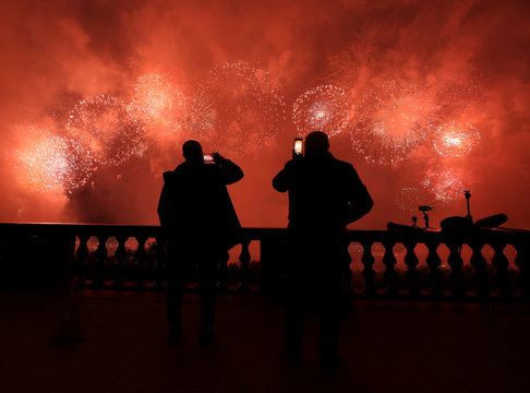 Spectators watch as fireworks explode in the sky as part of celebrations on Victory Day in Moscow