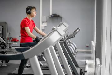 Fototapeta young man in sportswear in the gym on a treadmill