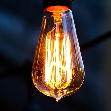 Close-up Of Illuminated Light Bulb Hanging In Darkroom