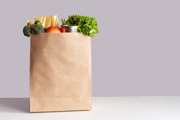 Various grocery items in paper bag on white table opposite gray wall. Bag of food with fresh vegetables, fruits, pasta and canned goods. Food delivery, shopping or donation concept. Copy space.