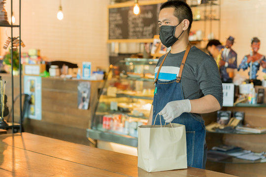 Waiter serving takeaway food to customer in small business social distance conceptual.
