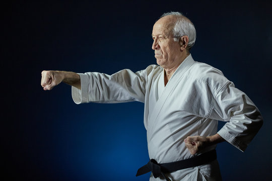 On a blue background, an old man athlete beats a punch arm