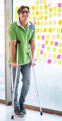 Young handsome student with crutches in conflicting priorities c