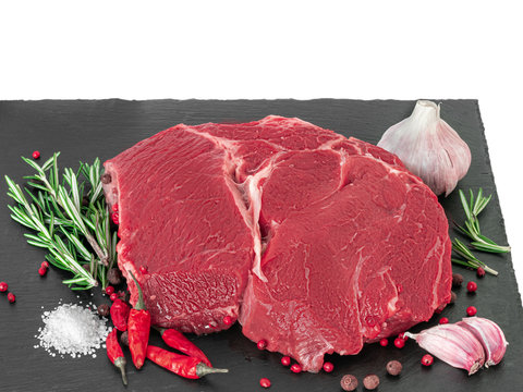 Beef and spices. Raw beef steak with spices on a dark board, isolated on white