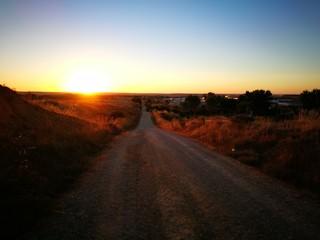 Foto auf Acrylglas Schwarz Empty Road Along Countryside Landscape At Sunset