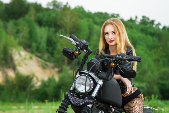 Young sexy girl in leather jacket sitting on black motorcycle. beautiful blonde woman and motorbike. biker girl posing on custom bike on summer day.