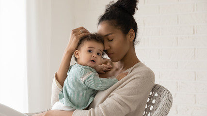 Portrait of young african American mother hold hug little toddler baby relax together in chair at home, happy biracial mom embrace small newborn infant child show love and care, childcare concept