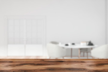 Table in blurry white dining room with door
