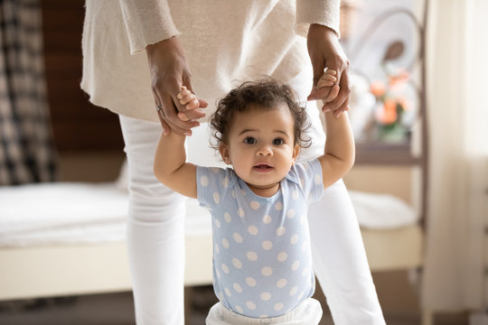 Portrait of cute small african american baby girl learn walking at home holding mom hands, little biracial toddler infant child make do first steps with mother support, childcare, upbringing concept