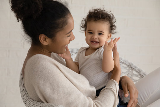 Loving young african American mother hold embrace cute little ethnic infant toddler, caring biracial mom play have fun hug small baby child, enjoy family time at home together, childcare concept