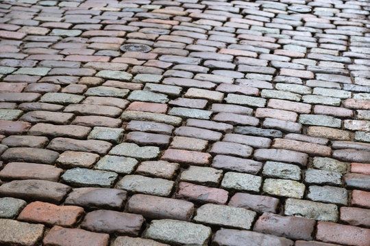 """""""Natural paving granite stone on road. Paving stone in old city. Wet boulder.."""""""