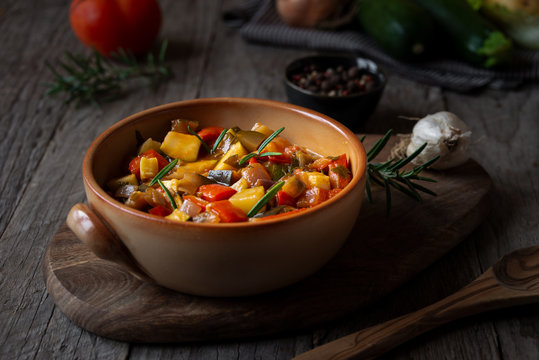Chopped cooked vegetables on dark wood. Traditional ratatouille with zucchini, bell pepper and eggplant