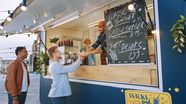 Food Truck Employee Hands Out a Freshly Made Gourmet Burger to a Happy Young Man in a Suit. Street Food Truck Selling Burgers in a Modern Hip Neighbourhood.