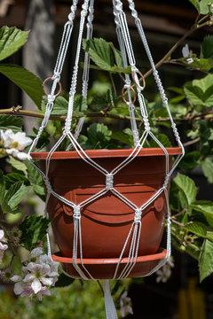 Fragment of a white macrame nylon thread planter for a flower pot suspended in the garden
