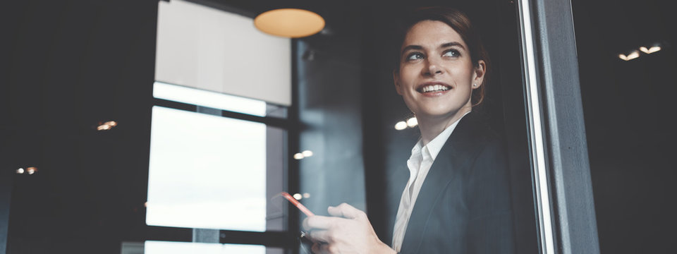 Portrait of charming business lady working in big open space office. Wide screen, panoramic