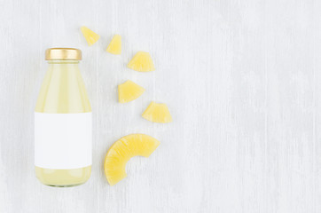 Fresh pinapple yellow juice in glass bottle with blank label, sliced fruit on white wood board, top view, copy space, mock up for design, advertising, portfolio.