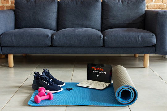 Fitness sports equipment and laptop over home living room background. Home online workout concept.