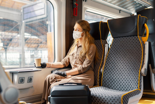 Woman wearing white protective face mask is using public transportation during the epidemic outbreak