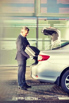 Portrait of mature businessman putting his suitcase on car trunk