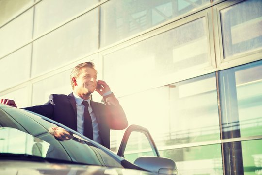 Portrait of Businessman standing outside his car while talking on smartphone