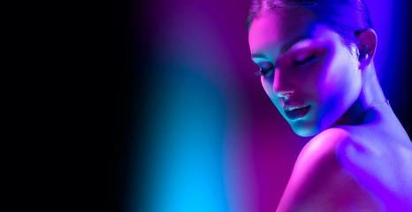 High Fashion model woman in colorful bright neon lights posing in studio, night club. Portrait of beautiful girl in UV. Art design colorful make up. On colourful vivid background, art design.