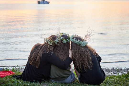Three girls with wreaths of wild flowers by the lake. An evening at Saint John's Eve by the lake.