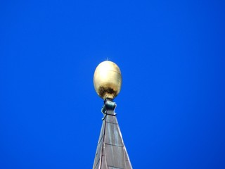 Golden sphere as lightning arrester with blue sky background and copy space