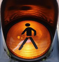 Closeup of a yellow pedestrian light with walking stickman as warning sign