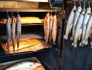 Fresh smoked fish hanging in a smoker on hooks, for sale on a weekly market