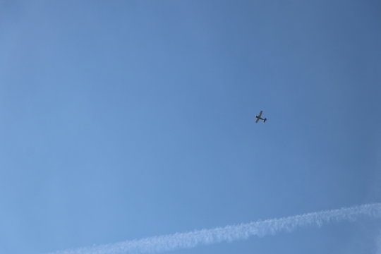 Small airplane and contrail on clear blue sky as background with copy space