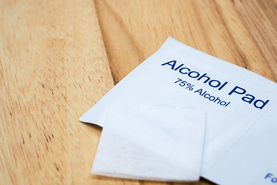 The close-up 1 unused alcohol pad over 2 alcohol pads in a package which are 75% alcohol with wood table background under warm light.