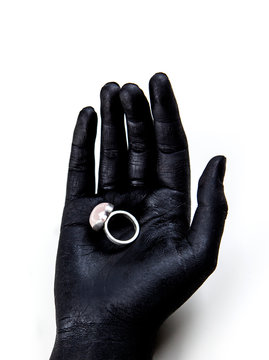 Black painted hand holding a silver ring