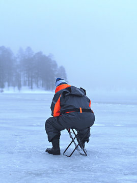 Lonely ice fishing man sitting on a foggy lake in Lapland, Finland