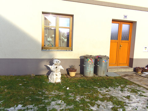 Sad melting snowman in spring