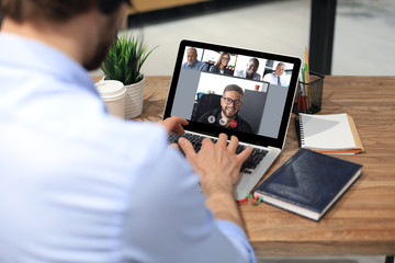 Businessman speak talk on video call with colleagues on online briefing during self isolation and...