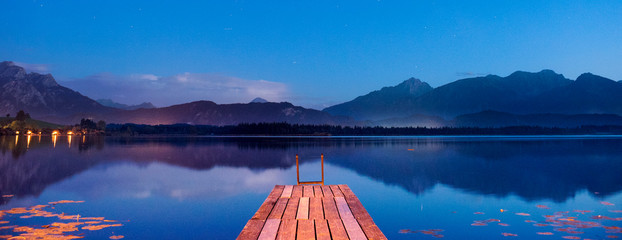 wooden jetty in lake with mountain range at sunset