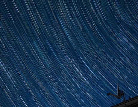 Satellitenantenne vor Nachthimmel mit Sternenspuren